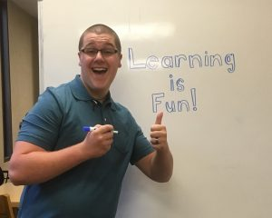 "William Wright, standing in front of a whiteboard that reads ""learning is fun."""