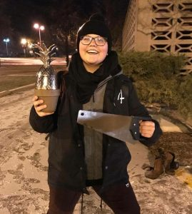 Riley Jones, bundled up for the winter, holding a metal pineapple in a flowerpot in her right hand and a saw in her left.
